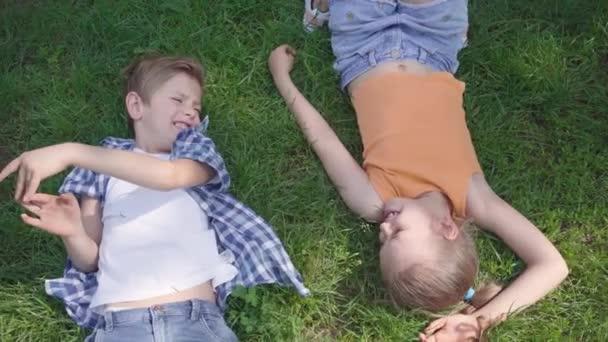 Porträt zwei lustige süße entzückende Kinder, die auf dem Rasen im Park liegen und einander anlächeln. Lustiges Mädchen, das den Jungen an die Hand nimmt. ein paar glückliche Kinder. lustige unbeschwerte verliebte Kinder. Ansicht von oben