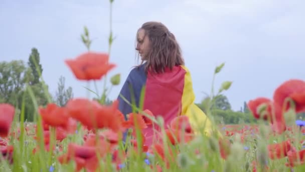 Cute adorable cute young woman standing in a poppy field holding flag of Germany in hands outdoors. Connection with nature, patriotism. Leisure in nature. Blossoming poppies. Freedom.