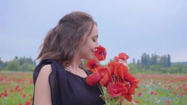Portrétní mladá žena, která drží a čichá kytici květin v dlaních a dívá se do kamery, stojící v makové oblasti. Souvislost s přírodou. Zelená a rudá harmonie. Volný čas v přírodě.