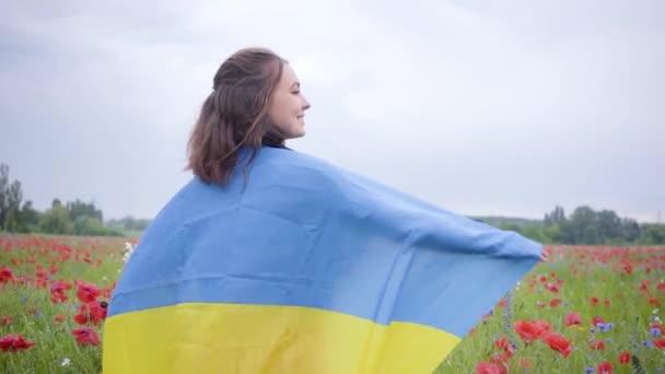 Roztomilá mladá dívka, která stála na májním poli s vlajkou Ukrajiny. Souvislost s přírodou, vlastenectví. Svobodný duch, emoce, vášeň. Volný čas v přírodě. Kvetoucí koláč. Svobody