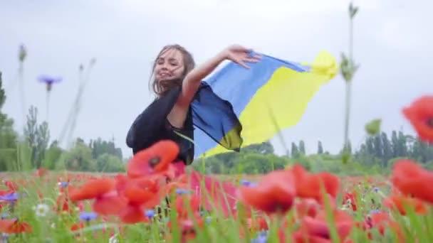 Portrét rozkošná mladá žena tančící v makku s vlajkou Ukrajiny v rukou venku. Souvislost s přírodou, vlastenectví. Volný čas v přírodě. Kvetoucí koláč. Svobody.