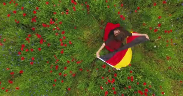 View from above of young girl dancing in a poppy field holding flag of Germany in hands outdoors. Connection with nature, patriotism. Leisure in nature. Blossoming poppies. Freedom.