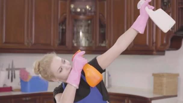 junge schöne Frau, die Flaschen Spülmittel in die Höhe hält und herumalbert. Putztag. Hauswirtschaft Hausarbeit und Reinigungsservice-Konzept
