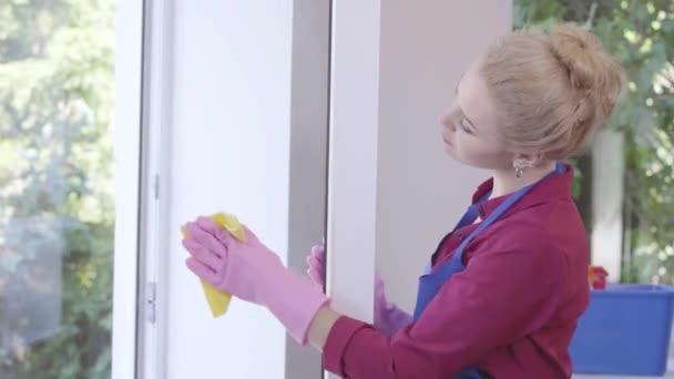 Roztomilá mladá dáma s čisticím oknem. Koncepce úklidové práce v domácnosti a úklid.