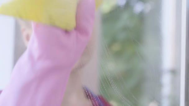 Nahaufnahme des müden blonden Mädchens beim Fensterwaschen mit Fensterlappen im Zimmer. Putztag. Hauswirtschaft Hausarbeit und Reinigungsservice-Konzept.