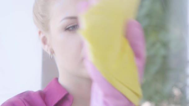 Nahaufnahme des Gesichts einer müden blonden jungen Frau, die im Zimmer Fenster mit Fensterlappen wäscht. Hauswirtschaft Hausarbeit und Reinigungsservice-Konzept.