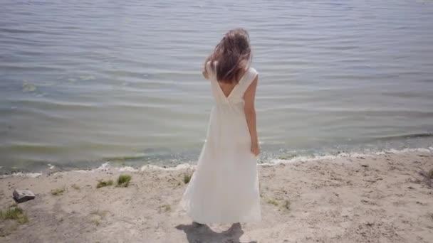 Porträt schöne junge Mädchen mit langen brünetten Haaren trägt ein langes weißes Sommermodekleid am Fluss stehen. Freizeit hübsche Frau im Freien.