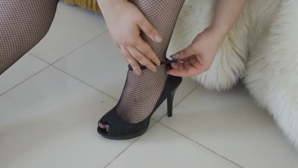 Female zips up the shoe on her plump leg in stocking sitting on the bed close-up. Hot fat lady preparing for the date. Erotic, overweight, plus size