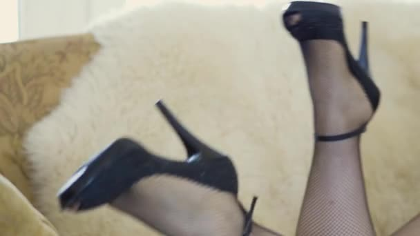 Confident unrecognized plump woman liying on the couch and flirtily waving her legs in tights in a mesh or stockings and heeled shoes