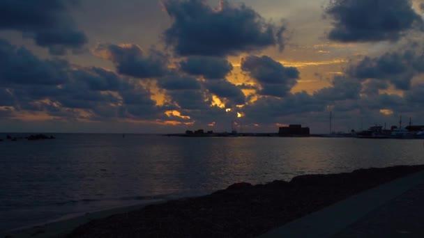Výhled na malebnou pobřežní krajinu s pestrým nebem a na letní západ slunce vytváří čisté vlny moře. Zpomaleně. Kypr.