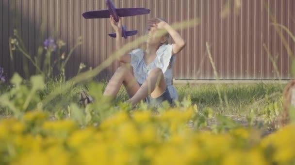 Aranyos lány egy játék sík ül a zöld fű az udvaron. Lány szórakozik a szabadban. Gondtalan gyermekkor. Lassított mozgás