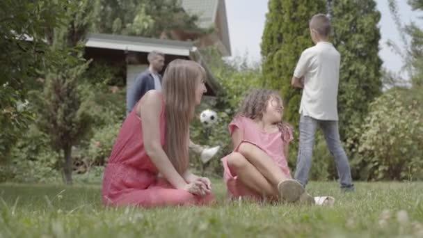 Porträt einer glücklichen Familie, die gemeinsam Zeit im Garten verbringt. Mutter und Tochter sitzen im Vordergrund. Vater und Sohn spielen im Hintergrund den Ball. Sommerfreizeit