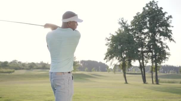 Portrét pohledného úspěšného Středního východu golfista, který se houpal a udeřil golfovým míčkem na nádherný kurz. Sebevědomý muž golfingu v krásném slunném letním počasí na slunci.