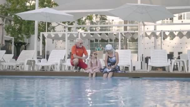 glückliches älteres Paar mit kleiner Enkelin am Rande des Luxus-Pools. Großmutter, Großvater und Enkel unterhalten sich. glückliche freundliche Familie. Erholung im Hotel. Erholung und Freizeit im Freien