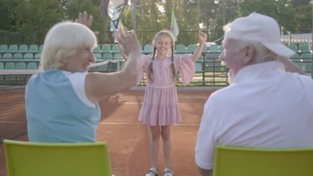 Pěkná srandovní dívka se dvěma pigocky vyhrála tenisový turnaj. Její prarodiče sedí blízko u kamery, která podporuje vnučku. Milé dítě zvednutí povyku ve vítězné gesto