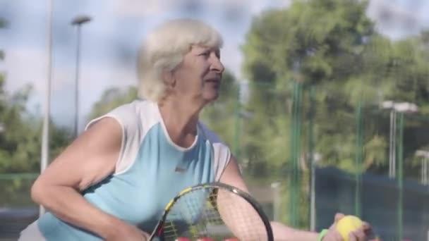 Zralá koncentrovaná žena, která drží rámus a míč na tenisový kurt. Aktivní volný čas venku. Střelba za tenisovou sítí