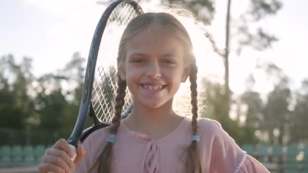 Na portrét roztomilá malá usměvavá dívka s copánky a tenisový randál na rameni, která se dívá do kamery stojící v paprscích letního slunce. Rekreace a volný čas.