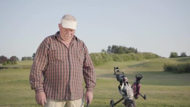 Starší muž odfoukne prach z golfového klubu, zničí to před zápasem. Starý pán hraje hru venku. Letní čas