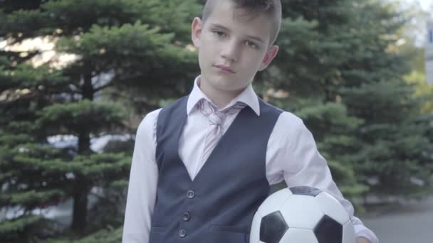 Porträt niedlichen gut gekleideten Jungen, der auf der Straße mit dem Fußball und der Handtasche stehen. ernsthafter junger Mann, der sich gleichzeitig wie Kind und Erwachsener verhält.