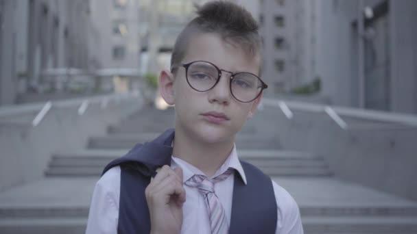 gutaussehender, gut gekleideter Junge mit Brille, der auf der Straße steht und in die Kamera schaut. ernstes Kind vor einer wunderschönen Stadtlandschaft mit hohen Gebäuden, Wolkenkratzern. Kleinstadtbewohner. Kind als Erwachsener.