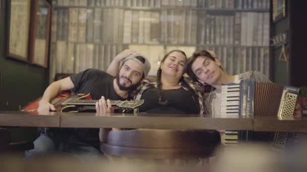 Young bearded man with guitar and his friend with accordion put their heads on the chest of a fat girl sitting on the sides of her. Leisure at the pub. Friends having fun together