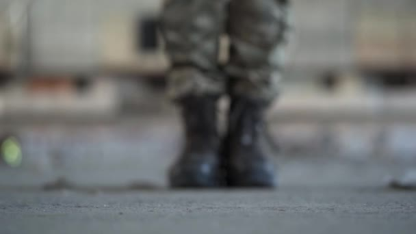 Feet of the soldier in old boots making a step forward on the dusty dirty concrete floor in an abandoned building. Volunteer concept