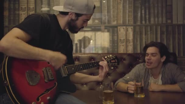 Young positive bearded man playing guitar in the bar, his male friend sitting near shaking his head in the rhythm. Leisure at the pub. Guys having fun together drinking beer