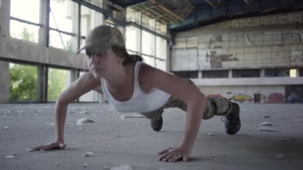ziemlich starke selbstbewusste junge Frau in Militäruniform Liegestütze in einer verlassenen Fabrik. Im Vordergrund stehen hochhackige Schuhe. Teil seines Cross-Fitness-Workouts. Intervalltraining mit hoher Intensität.
