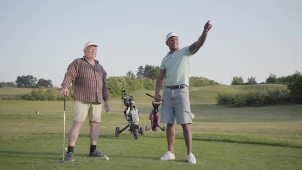 Zralý Kavkazský muž a mladý muž středního východu hrající Golf na golfovém hřišti. Muži se posunují ke straně, vypadají a diskutují. Letní čas.