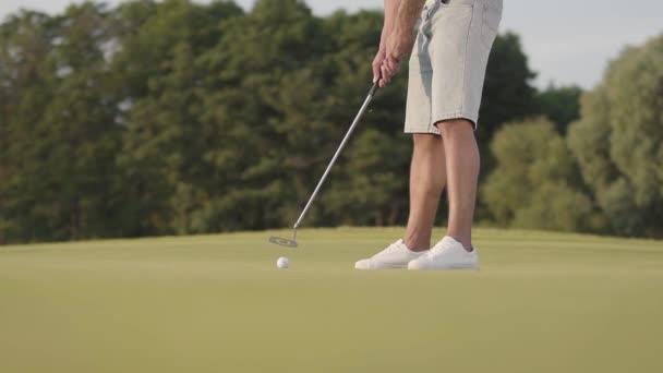 Nerozpoznaný muž hrající Golf na golfovém hřišti. Sebevědomý muž se zahřívá a udeřil do míče pomocí golfového klubu. Pojetí rekreace a sportu venku. Zpomaleně