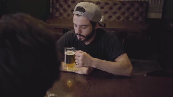 Two men drinking beer sitting at a table in a pub. Guys having fun together.