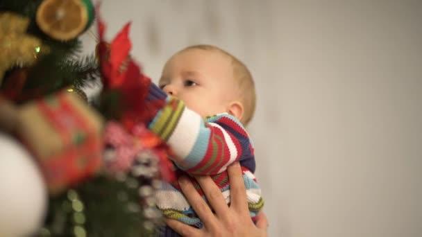 Papa und Baby schmücken den Weihnachtsbaum. glückliche Familie feiert Weihnachten zusammen. Zeitlupe.