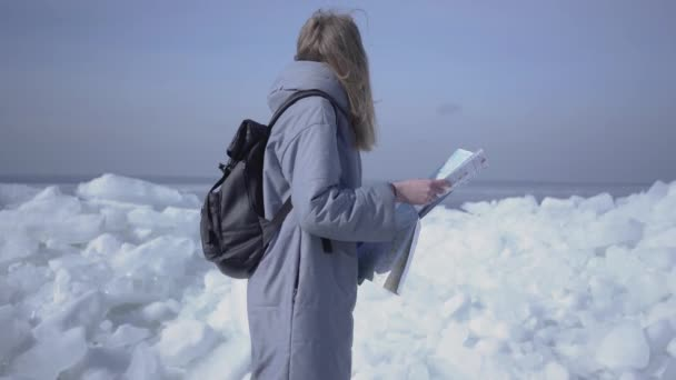 Attractive blond woman with backpack checking the map in front of ice at the North or South pole. Tourist travels in the winter. The girl is lost and wants to find a way