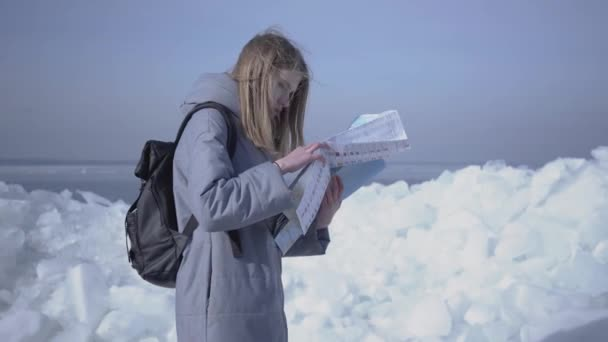 Young blond pretty woman in warm jacket standing on the glacier checking with the map. Amazing nature of snowy North or South Pole. The tourist in front of the ice blocks. Lady is lost