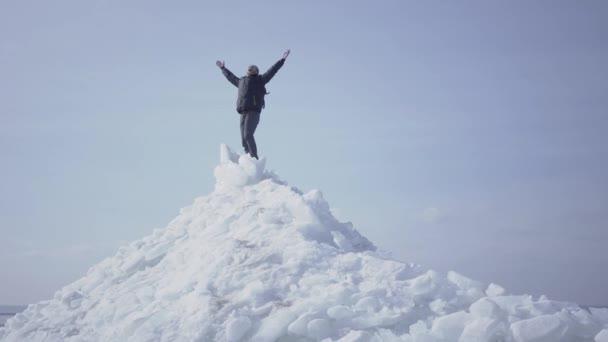 Emocionální šťastný muž v teplém kabátě, který stojí na vrcholku ledovce, hází ruce a vítězně zvítězil. Nádherný výhled na zasněžený Severní nebo jižní pól. Samec je na ledové kostce. Ten chlap dosáhl vrcholu