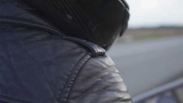 Unrecognized motorcycle rider in black leather jacket and helmet sitting on a motorcycle outdoors. Hobby, traveling and active lifestyle. Leisure and travel by motorcycle