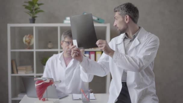 Zwei männliche Ärzte bei der Röntgenuntersuchung im Büro einer modernen Klinik. Der jüngere Mann im Arztkittel zeigt seinem älteren Kollegen ein Röntgenbild und bittet um Rat und Zustimmung. Konzept der medizinischen Behandlung