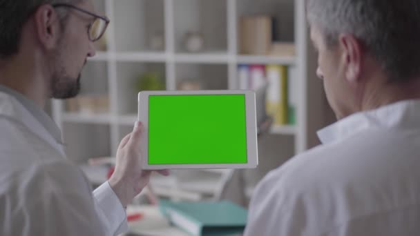 Two experienced male doctors checking information on the tablet, discussing. Concept of medicine, health care and people, hospital. New modern fully functional medical facility. Green screen.