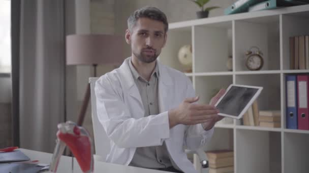 Portrait of handsome man in white robe looking in the camera showing tablet with picture of x-ray of lungs. Skillful doctor in modern private clinic. New fully functional medical facility. Slow motion