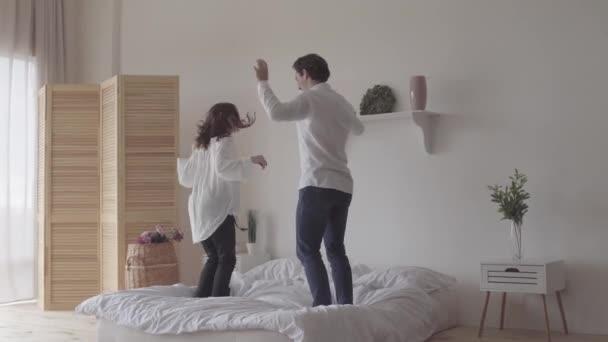 Boldog pár táncoló az ágyon a szobában otthon vagy szállodában együtt. Fiatal nő jumping és spinning körül boldogan. Egy szerető család szabadidőtöltési.