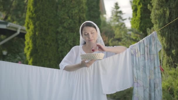 Pretty woman with white shawl on her head eating cherries looking at camera smiling over the clothesline outdoors. Washday. Positive housewife doing laundry. Slow motion.