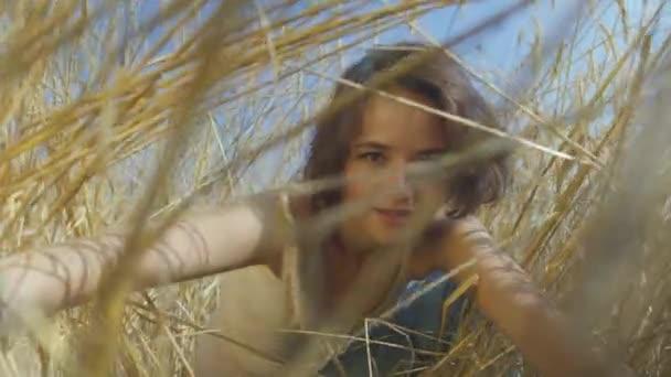 Roztomilá žena s krátkými vlasy na pšeničném poli. Dívka si užívá přírody a pózní v kameře. Sebevědomí bezstarostně opatrná dívka venku. Série skutečných lidí