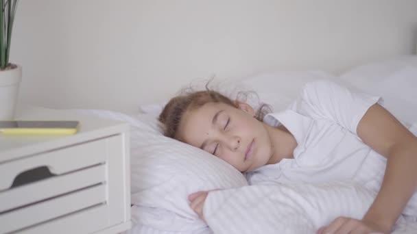 Aranyos kislány alszik az ágyban otthon. Egy lány felébred egy ébresztőóra a lány mobiloddal. Délelőtti idő. Felkészülés az iskolába. Gondtalan gyermekkor