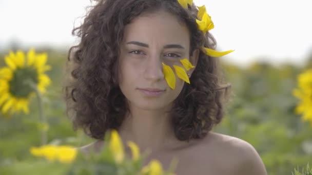 Portré csinos göndör játékos lány nézi a kamerát mosolygó állt a napraforgó területén. Élénk sárga szín. A lány magában foglalja magát a napraforgót. Szabadság koncepcióját. Boldog nő a szabadban