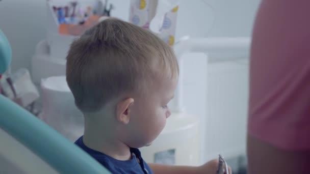 behandschuhte Zahnarzthände prüfen die Zähne des kleinen unbeschwerten Jungen, der auf dem Stuhl sitzt und ihm einen Spiegel in Großaufnahme zeigt. Stomatologie, Behandlung, medizinisches Konzept