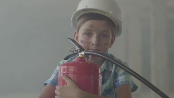 Portrét malého chlapce v bílé ochranné přilbě s hasicím přístroji, který se dívá na fotoaparát na pozadí kouře.