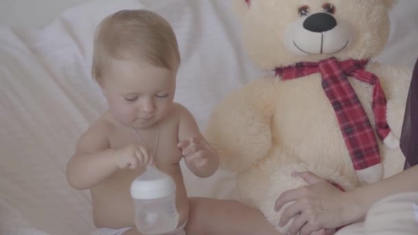 Cute young woman sitting with her baby girl who playing with baby bottle sitting in the bed, bid toy bear is near. Pretty baby girl drinks water. Concept of a happy family, motherhood. Slow motion