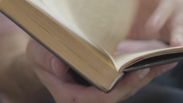 Großaufnahme männlicher Hände, die im Inneren des Buches blättern. Konzept von Wissen, Bildung, Freizeit zu Hause.