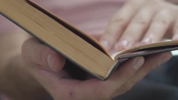 Male hands leafing through the pages of the book indoors close-up. Concept of knowledge, education, leisure at home.