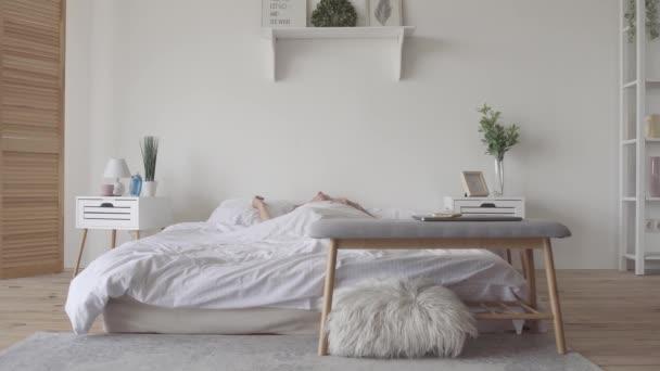 Krásná zralá bruneta se pomalu probouzí doma ráno, rozkládají se a sedí na posteli. Slunce na ní svítí z velkého okna. Šťastná bělošská žena si nový den.